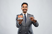 indian man realtor with house model and folder