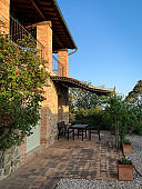Canopy with chairs and tables of a stone cottage in the Italian countryside.