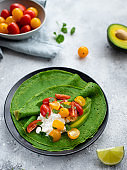 crepes with spinach, cottage cheese and fresh vegetables on a gray background.