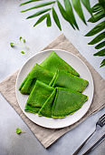 homemade crepes with spinach on a gray concrete background with green leaves.