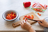 woman's hands cutting fresh bell peppers and putting them in a freezer bag