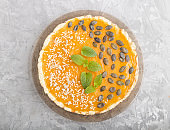 Traditional american sweet pumpkin pie decorated with mint, sesame and pumpkin seeds on a gray concrete background. top view, flat lay, close up.