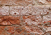 dried salt on a brick wall beside a canal in Venice