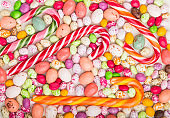 Colorful multicolored candies on a white wooden background. Christmas cane, chocolate eggs, caramel dragees. close up, top view, flat lay.