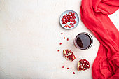 Glass of pomegranate juice on a white concrete background with red textile. Top view, copy space, flat lay.