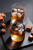 Glass of amber whiskey with ice and caramel candies on a black stone slate board on black background. Side view, close up, low key concept.