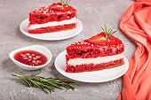 Homemade red velvet cake with milk cream and strawberry on a gray concrete background with red textile. side view, close up, selective focus.