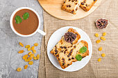 Homemade cake with raisins, dried persimmon and a cup of hot chocolate on a gray concrete background and linen textile. top view, flat lay, close up.