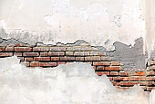 Texture of old brick wall and cracked stucco of white color
