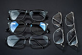Different types of glasses on a black background close up. Glasses with rectangular and round frames.