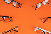 Different types of glasses on an orange background close up. Glasses with rectangular and round frames. Layout for design. Space for text and free space near the object.