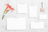 5 white different sizes watercolor sheets of paper taped on concrete background. Blooming orange lilies, wooden heart shaped key ring. Board, poster mockup on the wall. Flat lay, top view, copy space