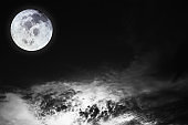 Black and white image of blurry cosmic clouds and bright full moon with stars on dark sky background. Image of moon furnished by NASA.