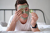 Young man in a white shirt with applied green cosmetic mask holding pieces of cucumber