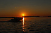 The boat floats on the sea at sunset