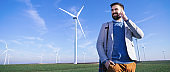 Young electric engineer outdoors in front of windmills