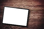Blank black digital tablet on wood background