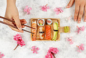 Somebody taking roll with chopsticks from a wooden tray