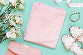 Mockup of a folded t-shirt placed surrounded by girly aaccessories and garments