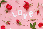 Red roses and text LOVE on a light pink background