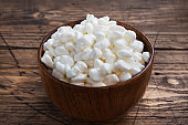 Fresh cottage cheese grain in a wooden bowl. Curd in granules with cream. Wooden rustic background. Copy space.