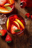 Fruit hot tea with the addition of oranges, lemons, strawberries mandarins and raspberries in a glass cups on a  wooden table.