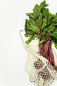 Trendy string bag with fresh young beetroot and haulm over light white background