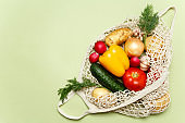 Trendy string bag with fresh vegetables and greens over light green background: potatoes, tomatoes, onion, bell pepper