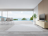 Rug on wooden floor of large living room and dining table near TV in modern beach house or luxury pool villa.