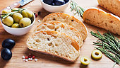 Italian ciabatta bread with olives and rosemary on a wooden Board.