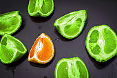 Different and standing out of the crowd fruit. Concept of leader. Healthy food - cuted pieces of juicy citrus fruits