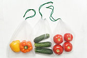 Reusable bags with, fresh vegetables tomatoes, cucumbers, bell peppers over white background