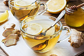 Two cups of natural herbal tea ginger lemon and honey on a wooden background.