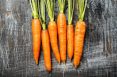 Close up of young fresh organic farmer carrots on rustic background, top view