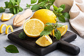 Juicy yellow lemons whole and cut with fresh mint leaves on a wooden stand. Close up.