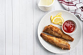 Fried fish hake Pollock with tomato sauce and slices of fresh lemon. Concept eating fatty fast food. White wooden table with Copy space.