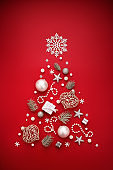 Christmas tree symbol made of white New Year decorations on red background.