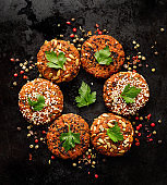 Vegan burgers, baked vegan burgers, cutlets made of carrots, millet, mix of seeds herbs and spices  on dark background, top view.