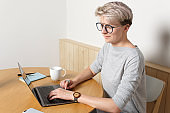 Young focused hipster millennial female with short blonde haircut working with laptop in cafe interior