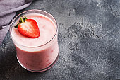 Homemade yogurt with fresh strawberries in glasses on a dark concrete background. Selective focus. Copy space.