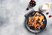 Belgian fluted waffles with fresh cherries and cream on a plate. Soft homemade waffles, sweet dessert with cherries. copy space