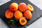 Ripe juicy apricots with mint leaves on a black slate Board, concrete background. Copy space.