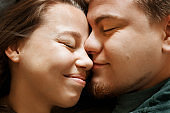 Emotional portrait of affectionate smiling kissing couple, close-up view