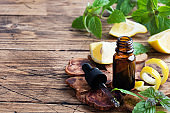 Lemon citrus fruit essential oil and mint, aromatherapy oil natural organic cosmetic on rustic wood background.