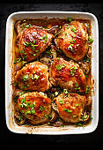 Roasted chicken thighs with mushrooms, garlic and herbs in a baking dish