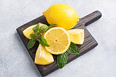 Juicy yellow lemons whole and cut with fresh mint leaves on a wooden stand. Copy space.
