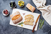 Italian ciabatta bread with olives and rosemary on a cutting Board. Dark concrete background.