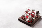 Stacks of vodka and cranberries on a wooden stand and background. Copy of the space. Bar alcoholic beverage tincture.