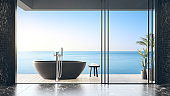 Black bathtub on wooden floor terrace of infinity pool in modern beach house or luxury villa.