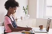 Little girl student drawing and studying online